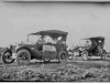 Print of two old cars with people (Model T era).
