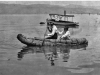 """"""" negative of two people paddling a tule boat."""